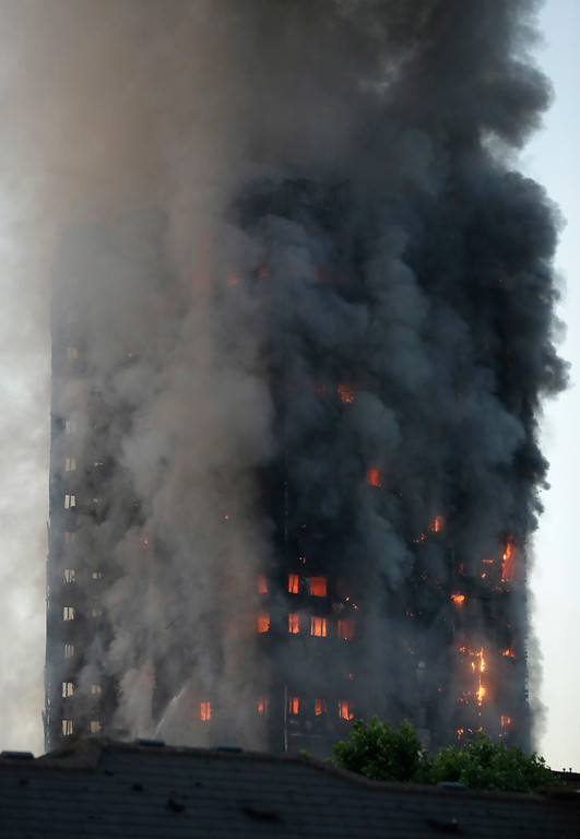 . Smoke and flames rise from a building on fire in London, Wednesday, June 14, 2017. Metropolitan Police in London say they\'re continuing to evacuate people from a massive apartment fire in west London. The fire has been burning for more than three hours and stretches from the second to the 27th floor of the building.(AP Photo/Matt Dunham)