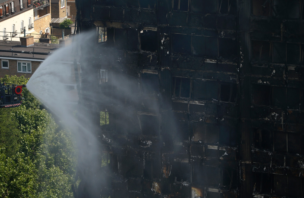 . A remote controlled aerial platform pours water onto any remaining fires inside a high rise apartment block in London, Wednesday, June 14, 2017.  A deadly night-time fire raced through a 24-storey apartment tower in London early Wednesday.(AP Photo/Alastair Grant)