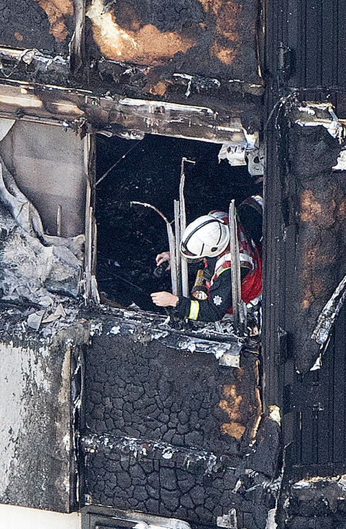 . A firefighter checks damage after a fire engulfed the 24-storey Grenfell Tower, in west London, Wednesday June 14, 2017. Fire swept through a high-rise apartment building in west London early Wednesday, killing an unknown number of people with around 50 people being taken to hospital. (Rick Findler/PA via AP)