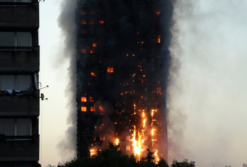 . Smoke and flames rise from building on fire in London, Wednesday, June 14, 2017. Firefighters are battling a massive fire in an apartment high-rise in London. (AP Photo/Matt Dunham)