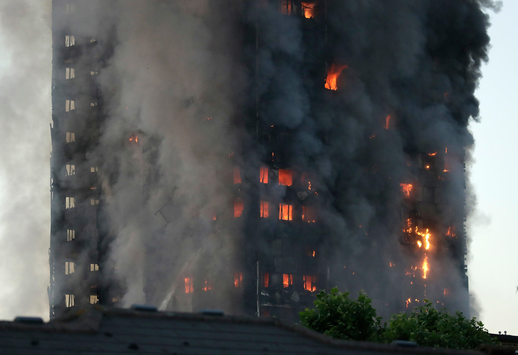 . Smoke and flames rise from building on fire in London, Wednesday, June 14, 2017. Metropolitan Police in London say they\'re continuing to evacuate people from a massive apartment fire in west London. The fire has been burning for more than three hours and stretches from the second to the 27th floor of the building.(AP Photo/Matt Dunham)