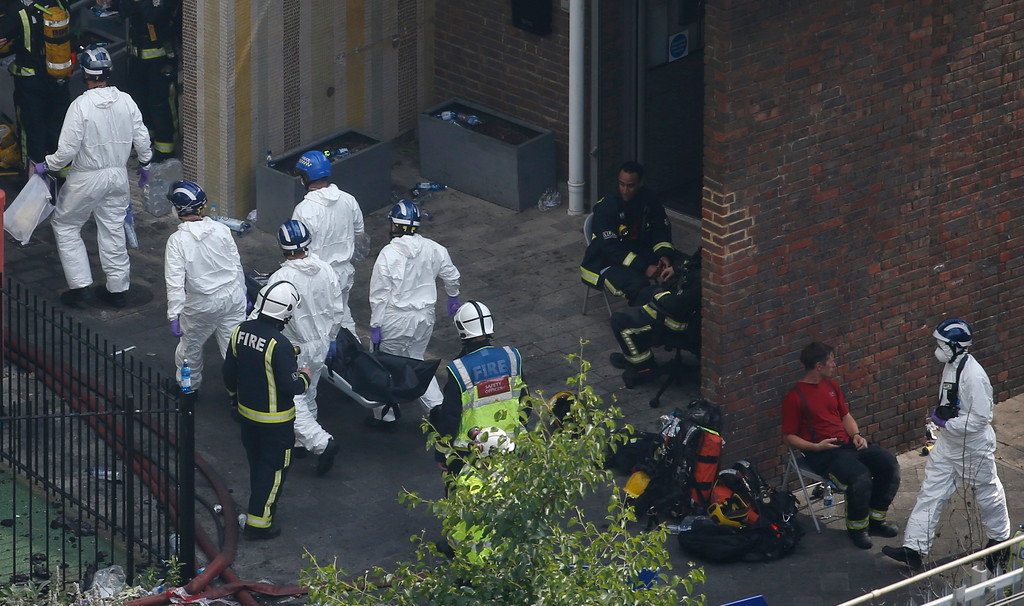. Forensic teams carry a body near the high rise apartment block that suffered a deadly fire in London, Wednesday, June 14, 2017.  A deadly night-time fire raced through a 24-storey apartment tower in London early Wednesday. (AP Photo/Alastair Grant)