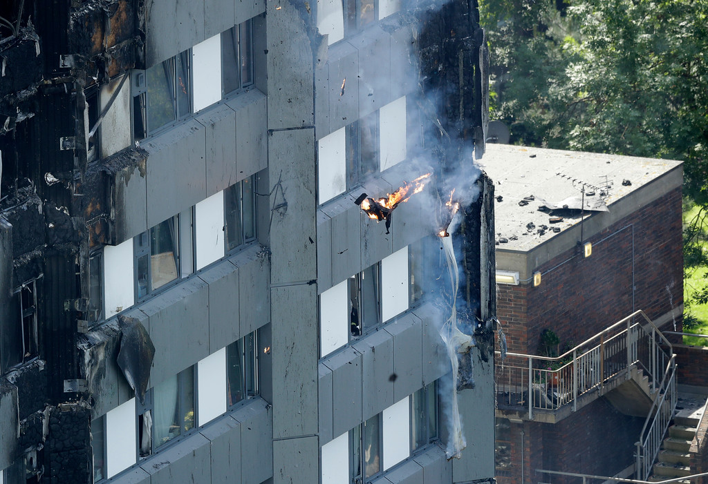 . Burning debris falls from a massive fire that raged in a high-rise apartment building in London, Wednesday, June 14, 2017. A deadly night-time fire raced through a 24-story apartment tower in London early Wednesday, killing at least six people and injuring dozens more. (AP Photo/Matt Dunham)