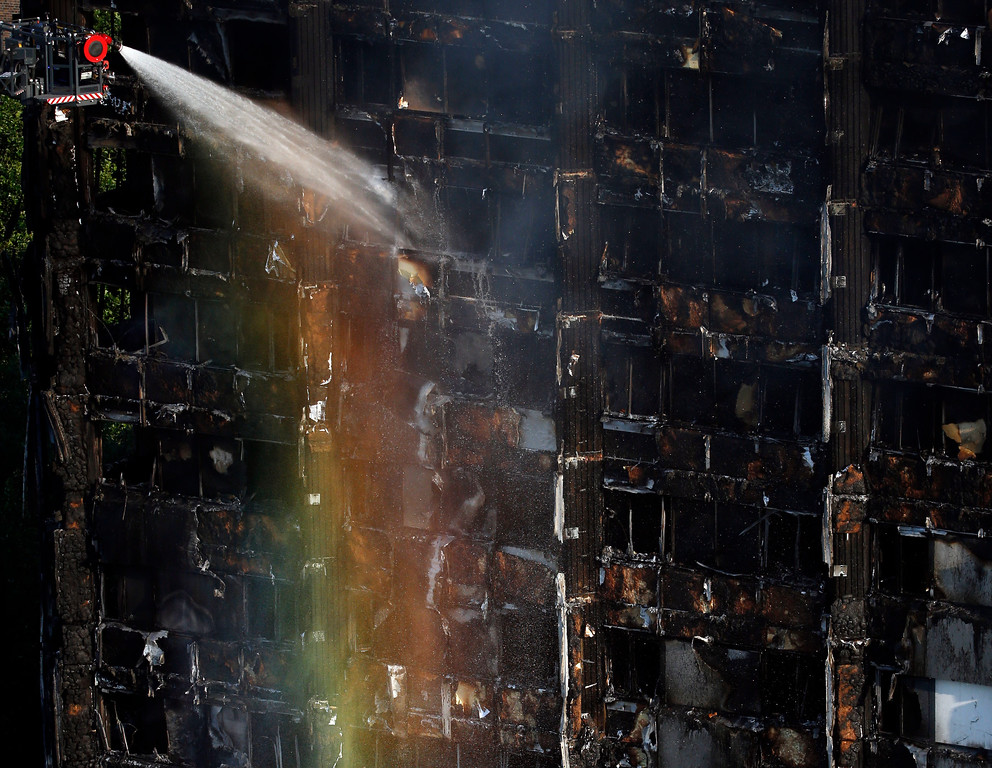. The sun creates a rainbow effect as firefighters work at the scene of a deadly blaze at a high rise apartment block in London, Wednesday, June 14, 2017. Fire swept through a high-rise apartment building in west London early Wednesday, killing an unknown number of people with around 50 people being taken to hospital. (AP Photo/Alastair Grant)