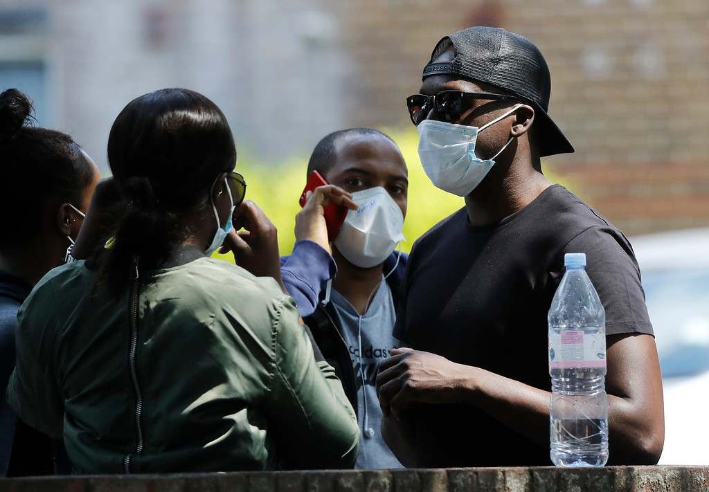 . People wearing masks for protection from the smoke stand near the high-rise apartment building where a massive fire raged, in London, Wednesday, June 14, 2017. A deadly night-time fire raced through a 24-story apartment tower in London early Wednesday, killing at least six people and injuring dozens more. (AP Photo/Frank Augstein)