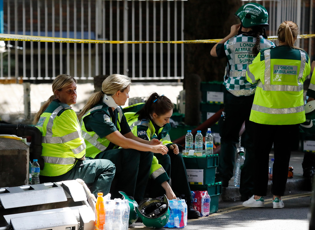 . Ambulance staff take a break near the high-rise apartment building where a massive fire raged in London, Wednesday, June 14, 2017. A deadly overnight fire raced through a 24-story apartment tower in London on Wednesday, killing at least six people and injuring more than 70 others. (AP Photo/Frank Augstein)