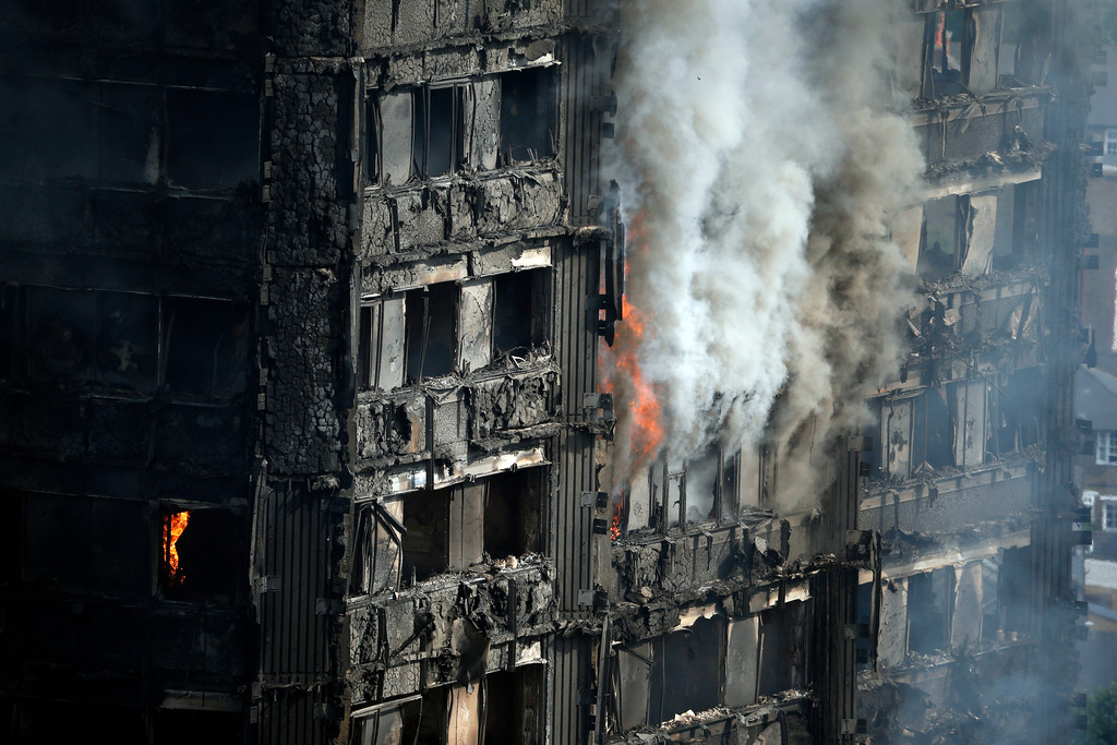 . Parts of the building still burn hours after a deadly blaze at a high rise apartment block in London, Wednesday, June 14, 2017. Fire swept through a high-rise apartment building in west London early Wednesday, killing an unknown number of people with around 50 people being taken to hospital. (AP Photo/Alastair Grant)
