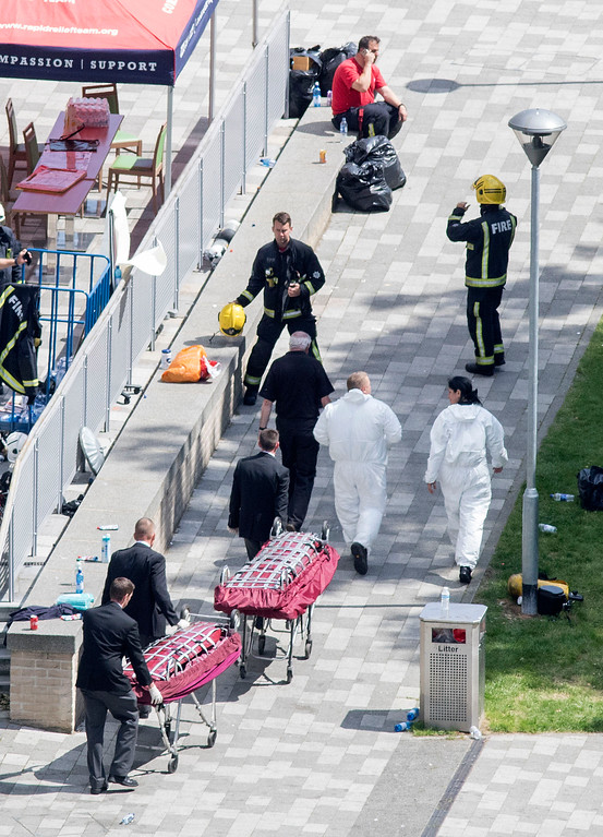 . Men push stretchers towards the scene after a fire engulfed the 24-storey Grenfell Tower, in west London, Wednesday June 14, 2017. Fire swept through a high-rise apartment building in west London early Wednesday, killing an unknown number of people with around 50 people being taken to hospital. (Rick Findler/PA via AP)