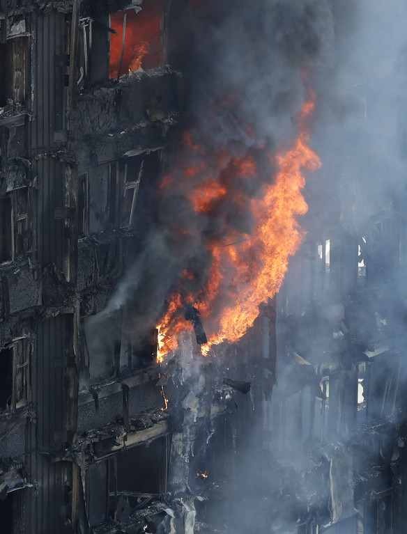 . Smoke and flames billow from a massive fire that raged in a high-rise apartment building in London, Wednesday, June 14, 2017. Fire swept through a high-rise apartment building in west London early Wednesday, killing an unknown number of people and sending more than 50 people to area hospitals. (AP Photo/Matt Dunham)