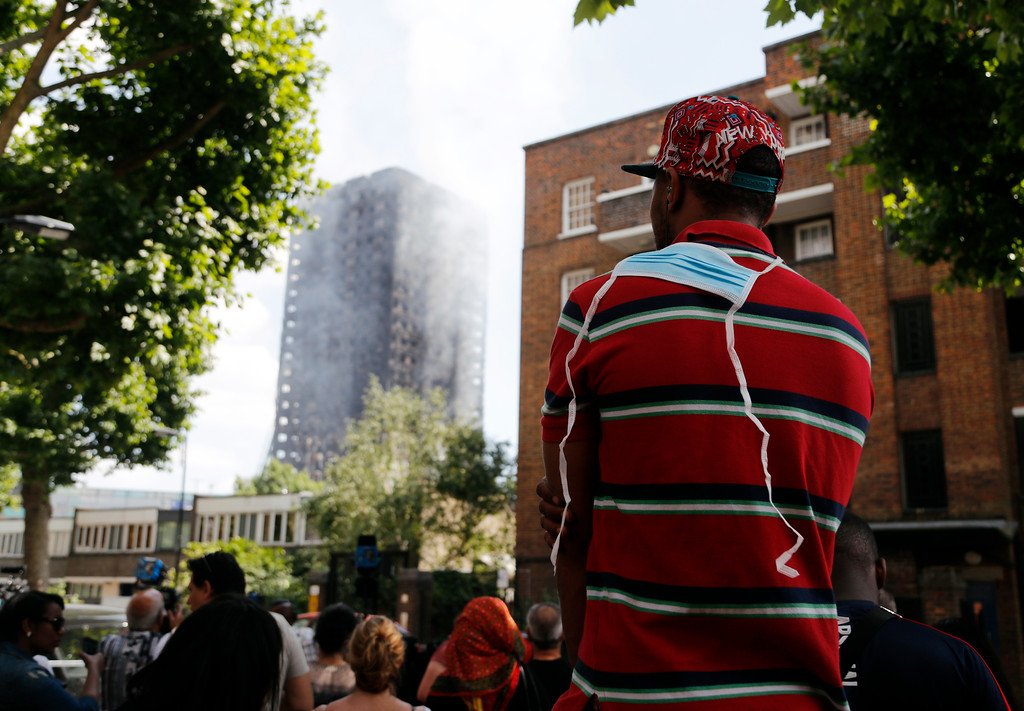 . A man looks across at the high-rise apartment building where a massive fire raged overnight, in London, Wednesday, June 14, 2017. A deadly overnight fire raced through a 24-story apartment tower in London on Wednesday, killing at least six people and injuring more than 70 others. (AP Photo/Frank Augstein)
