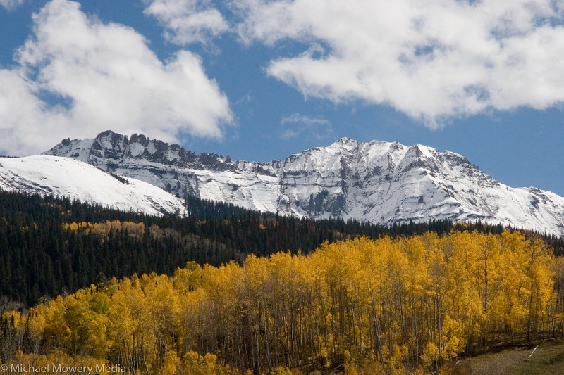 Snow covered Palmyra and Silver Mountain peaks over Aspens along Highway 145