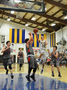 Gridley's Brian Wilkerson drives and scores with Las Plumas defenders, left to right, Sullivan Hurte (25), Ace Hindman (12) and Nick Greer (30) scrambling to defend as Gridley beats Las Plumas on the basketball court Friday, Feb. 3, 2017, in Gridley, California.  (Dan Reidel -- Enterprise-Record)
