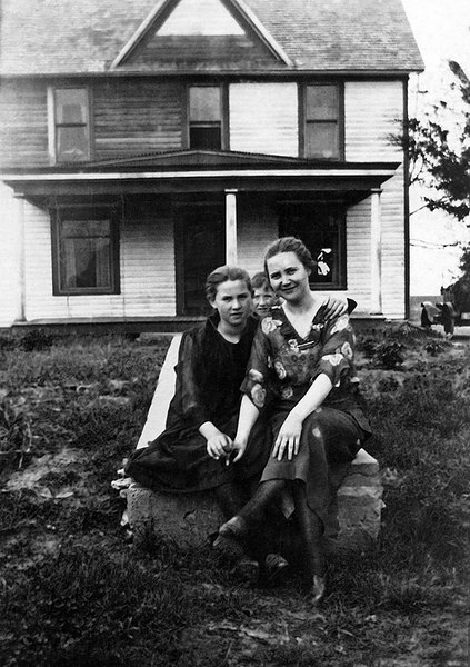 """1918 - Fire.  Dad has written on the back of this picture:  Hildreth Grigsby Root, James M. Grigsby and Josie Sweetwood Grigsby.  (This picture of our home at Williamsburg, Kansas shows where the house had been on fire about 1918.)  Josie was Theodore's first wife and the mother of Donald and Lida Margaret.  The picture of Hildreth (Dad's sister) is before she was married to Chet Root.  Hildreth was born in 1907 so she was  about 11 when this picture was taken.  Dad was born in 1910 so he was about 8.  The tree and weeds in the yard suggest it was summertime or fall?  The way the house looks and the kind of fire protection they probably had, it is a wonder the house didn't burn down completely!  We wonder what started the fire?  Lightning strike, """"coal oil"""" lamp?  Bill thinks that is Grandfather Will's 1912 or 1913 Buick that he used to deliver mail and we have seen in other photos."""