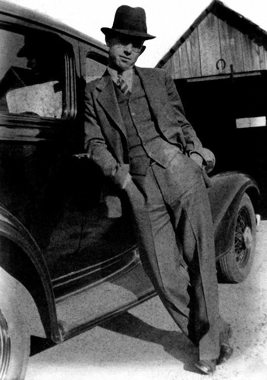 1932+ - 1932 Plymouth and James Maurice Grigsby.  This photo was in bad shape but Murry cleaned it up as well as he could because from his photographer's view point it shows a youthful swagger that we rarely saw from dad as we were growing up.  Murry loves the pose, the great facial reflection in the car's window and the horse shoe over the old garage opening.  The origin of the car is a mystery: 1) It could have been the car mom and dad used to move Lida Alma from Williamsburg to Denver in the summer of 1934 and belonged to Lida Alma?  2) Maybe dad bought it in Denver from Harry Lehman's Chrysler/Plymouth dealership where dad worked?  Bill doubts that the car was new when it was purchased so the photograph probably was taken sometime after 1932.