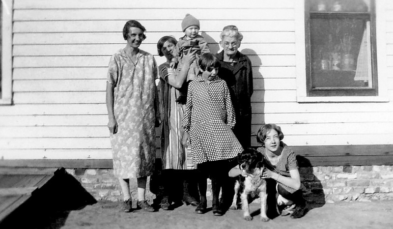 "1929 - This photo was probably taken in the summer of 1929 and Verna Mae wrote on the back of the photo:  ""Mother, Frankie, Verna, Mae, Inez and Junior.""  Kathleen Staten told Bill that mom and her family moved from the Killwinning, Missouri area in December 1924.  Bill is sure that ""mother"" is Lurena Taylor Staten (our grandfather, Chalmer's mother) who had traveled with her daughter, Frankie (Uncle Bennett's wife) from Missouri to visit and see her grandson, Chalmer Murry Staten, Jr. in Kansas.  So the people in the picture are from left to right, Verna Mae Staten, Frankie Staten Bennett holding Junior  (born about June 1929), Inez, Grandmother Lurena Staten, and ""Mae"" (our mother) holding the dog she called ""Pup.""  Bill is guessing that this house was in the Williamsburg, Kansas area because he has one of Mom's high school report cards for 1928-29 from Williamsburg High School in Franklin County.  Bill also has a May 4, 1926 6th grade report card for mom in an elementary school in district 70 of Franklin County.  Grandfather George Bechtel (Verna's father) lived near Baldwin City, Kansas in Douglas County.  Bill believes Verna and Chalmer followed grandfather George Bechtel to Kansas when he moved from the Killwinning, Missouri area.  Grandmother Lurena died in 1931.  Also, notice the outside entry to the ""basement"" or ""root cellar"" with a dirt floor but a place to go when tornadoes appeared. This basement was probably like the one we had at our 1276 South Pennsylvania Street house in Denver in 1940."