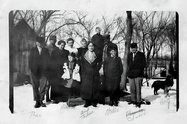 """1915 - This photo came from dad and he labeled the people in the photo with ink on the face of the image!!  Bill guessed that it was taken around Christmas 1915 because Hildreth is holding what looks like two new """"dollies"""" and there are no leaves on the trees.  Aunt Thelma was married to Frank Herring and she was about 5 months pregnant with daughter Lynette who was  born in April 1916.  The people in the photograph according to dad's labels are from left to right: Theodore Grigsby, """"Dad"""" (William Redman Grigsby), """"Mom"""" (Lida Alma), dad's  sister Hildreth, a question mark above the woman next to Lida Alma indicating dad didn't remember who that was, grandma Eva Hester Graves,  Aunt Thelma (Graves Herring -- Lida's younger sister), """"Bud"""" (James Maurice Grigsby about 5), grandpa George Selden Graves, Walter Grigsby, Charles Grigsby (whom dad labeled as Theodore his first try) and """"Dog.""""   Bill also believes the location was grandpa and grandma Graves' farm in Ohio Township of Franklin County Kansas where they lived in the 1910 and 1920 censuses.  Ohio Township is adjacent to and east of Williamsburg Township."""