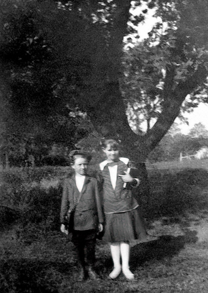 "1918 - Dad had written on the back of this photo:  James Grigsby, Hildreth Grigsby, about 1918.  That would make him 8 years old and Hildreth was 11.  Bill thinks this was the first day of school in Williamsburg in the fall of 1918 and dad was probably starting third grade.  Dad told a story about when he started school (It was first grade because there was no kindergarten then) and probably would have been 1916.  When his mother took him to school, he cried when she left him but shortly thereafter he left school too and went home by himself (they lived within easy walking distance of school).  Grandma Grigsby took him back to school again and again he came home.  We don''t remember the resolution of the problem but his father probably got him straightened out about attending school that evening.  Bill is impressed by the clothes that dad and Hildreth were wearing -- pretty fancy and suggest that William Redman was doing O.K. financially.  Check out dad''s satchel with the leather strap over his opposite shoulder and his ""jaunty"" cap.  He turned out to be a good student and we know personally how much he achieved by teaching himself accounting and becoming a CPA without a ""college"" education.  Pretty remarkable when you consider the situation he found himself experiencing in December 1933.  His father had died on Friday, October 6, devastating the family in difficult economic times.  His divorce from Neva Blair was final on December 1, 1933.  In a hand written letter to Neva dated December 16, 1933, he tells Neva that ""I am unable to pay $6 a month"" for child support.  What are the chances this story would have a happy ending?"