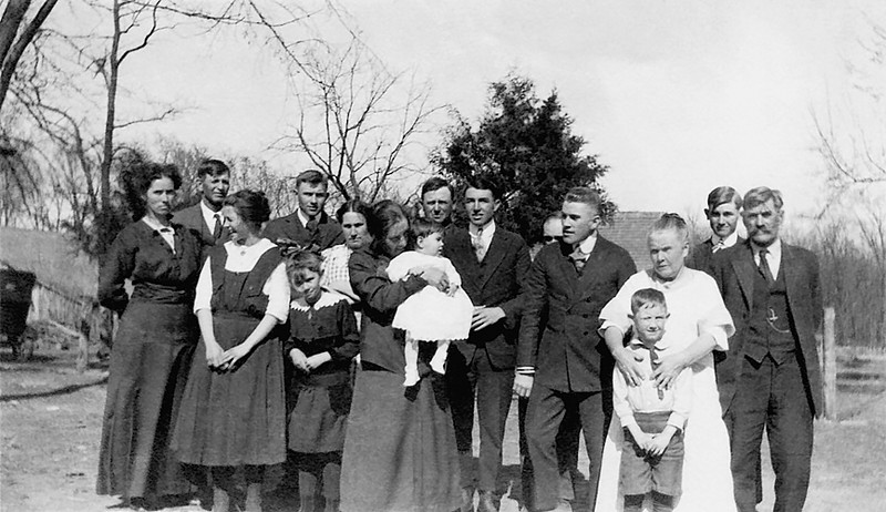 """1917 - Lynette Herring had a copy of this photo too.  Bill's copy of this photo came from dad and he had written on the back """"about 1917"""" and the people from left to right were:  """"The first three people are friends.""""  (Dad didn't remember who they were.)  Hildreth Grigsby Root, Theodore Grigsby, Lida Graves Grigsby, Thelma Graves Herring holding Lynette Herring, William R. Grigsby,  Charles Grigsby, Ezra Graves (barely visible), Bruce Graves, Eva Hester Graves holding dad, Walter Grigsby, George Graves.  On the basis of all five pictures of this event that dad gave Bill, he believes this gathering took place about Thanksgiving, November 1916, at our grandfather William Grigsby's homestead near Williamsburg (which was a short distance out of town then).  Lynette thought the gathering had occurred in """"1916-1917"""" on """"Grandpa Graves' farm near Baldwin City, Kansas.""""  However, in both the 1910 and 1920 Kansas censuses, grandpa Graves lived in Ohio Township of Franklin County near Williamsburg but Baldwin City is in Douglas County north and west of Franklin County.  The TGOD photograph of Lynette in her baby carriage in this series of images tells us that this photo was taken at William Redman's home (his Buick and horse-drawn mail carriage are parked behind Lynette sitting in her baby buggy) and that Lynette was about 7 months old and not yet walking having been born in April 1916.  However, Lynette thought the 3 people whom dad identified as """"friends"""" may have been some of William Redman's relatives on grandma Spring's side of the family (i.e., Will's half sister,  Sue Anna Spring Keenan,  her husband, Thomas Keenan and their daughter, Mary Keenan).  Bill has a photo from Norman Spring of Sue Anna and Mary and he thinks Lynette is correct about who dad's """"friends"""" were."""