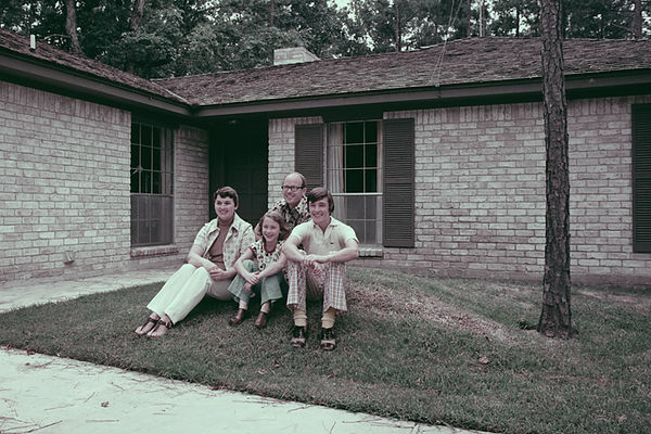 1974 - Murry's family moves to Texas:  1974 photo of Pat, Jodi, Murry and James in front of the new house in Montgomery County, Texas.  We moved from Arvada, Colorado where we spent many a weekend camping in the Rocky Mountains.  Since this property was just 60 feet above sea level we built a burm in the front (the bump we are using for the pose) and called it Mount Grigsby.