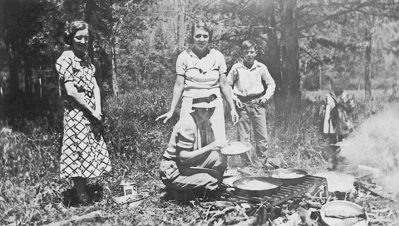 """1936 - Colorado Picnic.  This photo shows from left to right Elma Mae Staten Grigsby, Josie Sweetwood Grigsby (kneeling to cook), """"Bill"""" King (wife of Harry King and good friends of Elma and James Grigsby in Denver), Donald Lee Grigsby, son of Theodore and Josie Grigsby (born August 15, 1922) and Lyda Margaret Grigsby (Walsh) who is the younger sister of Donald.  The back of this photo from Donald Grigsby states that the print was made August 28, 1936 by Bio-Tone Prints in spite of the hand printed date, 1937, on the face of the picture.  The picture was taken at a picnic in Colorado perhaps somewhere around Pine, CO where the Kings had a cabin. Bill and Murry visited the cabin with our parents and Harry King had a bear skin rug made from a bear he had shot.  I believe the Kings might have lived in Denver after this time and later moved to Grand Junction where we remember visiting them."""