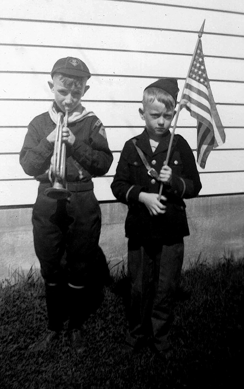 1943 - Bill and Murry, Patriots:  Photo taken in the backyard at 2566 South Washington Street.  Bill in his scout uniform with the Rosedale Elementary school bugle that the color guard members got to bring home.  Murry in some kind of military uniform that was probably used to quiet the complaining about not being in the scouts?  The flag was the mystery gift from Uncle Charles (NOT).  I was supposed to get a roll-top desk for my birthday but after trying to burn down the garage I only got a flag and then the folks said it was from Charles.  They should have let me in the scouts because I knew how to make a fire :0)