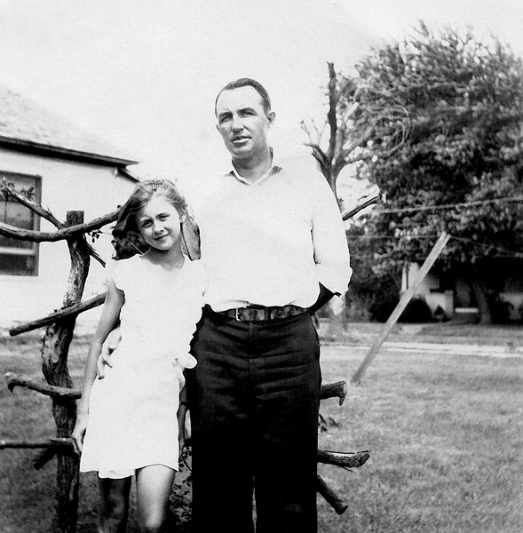 """1929 - This  picture shows Phyllis when she was about 9 years old with her father, Charles Grigsby.  I'm pretty sure that this picture was taken someplace other than our Grigsby Grandparents' house in Williamsburg -- maybe at Phyllis' Greeve Grandparents.   The time would be about 1929 and I know that Charles was living in Richmond, Kansas in 1933 when Grandfather Will Grigsby died.  What is the """"contraption"""" behind them?  I thought it might be a basket for tomatoes to grow up and Murry suggested a grape support or for climbing flowers."""