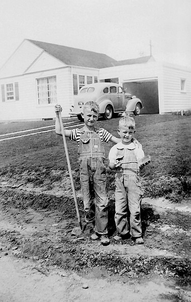 """1941 - Bill and Murry as the landscapers 1941.  This photograph was probably taken sometime in 1941 and Bill titled it """"Brotherly Love.""""  Bill remembers chopping weeds with a hoe so maybe that was what we were supposed to be doing before the picture was taken.  If it was 1941, Murry was 4 and Bill would be 7 in October.  Once again the older sibling gets the good stuff -- check out the little shovel Murry has to chop weeds (or smack Bill) while Bill gets a regulation hoe!  Bill likes the pose — do you suppose mom suggested that or was it spontaneous?  It also shows what a mess our street was until after the war in about 1947 when sidewalks and asphalt pavement for the street arrived.<br /> We were standing in front of Frank and Wilma Sherman's house at 2572 South Washington street next to and south of our house at 2566 visible behind us in this image.  This photograph showed a better view of the 1938 Plymouth that had hydraulic brakes and the gear shift on the floor.<br /> The Sherman kids were Walter and Nadene.  Walt was a year older than Bill and Nadene was the same age as Bill and in the same grade at school.  We attended Rosedale Elementary School which was about a seven block walk from our houses.  The other kids in the neighborhood included Bobby Daniels and his sister, Becky, the Liston brothers, Tom, Dick and Harry, Roger McNall and his sister, Charleen (?), the Tatman brothers, Bobby and ?, the Lowe sisters Julie and Pat, the Hansen brothers Billy and ?, Larry Peterson, the Houck kids (Tommy and?), Phil Brown, David Kelley, John Prather, Dick and Chuck Woods, Bobby and ? Pelham, Joann and Pat Thompson, Pat and Jerry Miller and the three Fuller brothers (maybe Larry, Curley and Moe?).  There were lots of kids walking to school in the mornings and there was always someone available for outdoor playing including batting, throwing and kicking balls, hide and go seek, tag, riding bicycles, etc."""