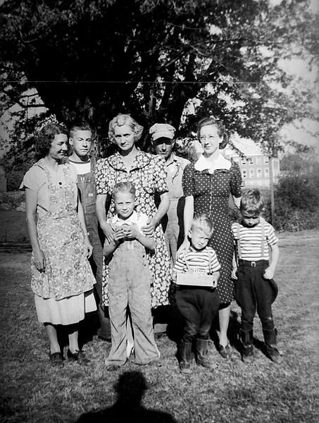 """1941 - The people in this 1941 photograph are from left to right: grandmother Verna Mae Bechtel Staten,  Chalmer Murry Staten Jr.  (""""Junior"""" was 16 on June 16, 1941), aunt Effie (Effie Elzira Staten Weldon Rowe), Vern Martin (Effie's grandson by daughter Marjorie Weldon Martin and Virgil Martin), Chalmer """"Red"""" Weininger (Kathleen believed that's who it was but she wasn't sure?), Murry Grigsby, Elma Mae Staten Grigsby and Bill (happy face) Grigsby.  Bill concluded that he was angry because he didn't get to hold the box and toy bus!!  Also, you can see the Downing school building in the background over Elma's left shoulder.  This photo was made in front of Verna and Chalmer's house in Downing, Missouri where we visited several times over the years.  The house was a converted garage because the cement driveway still led up to their front door.  Bill's recollection was that they had a swing on one of the trees in front of the house and that there was no in-door plumbing so we had to use an outhouse.  At least the hand pump for the well water was inside the kitchen.   Bill remembers that Vern Martin was mean (terroized) to us when no one was watching.  This also could have been the time that dad took Bill, mother and Murry to Lancaster, Missouri, about 5 miles west of Downing, where we boarded the milk/passenger train to ride back to Downing on our very first train ride.  Grandpa Chalmer said it was a tri-daily train.  If it didn't show up today they'd try again tomorrow.  Bill remembers that when Vern Martin was a teenager he was crushed between a couple of corn wagons during harvest time and he died from his injuries.  Whose shadow is that taking the photograph?  Those ears could be Grigsby ears and may belong to our dad, James Grigsby who's not in the photograph but was present during this adventure."""
