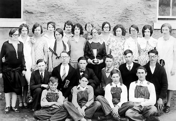 "1929 - This photo of mom and dad was made sometime in the spring of 1929 when dad was a senior at Williamsburg High School and mom was a sophomore.   Mom is holding the trophy for first place for a scholastic competition.  Dad is kneeling in the second row wearing his letter sweater.  The accompanying information says: ""In 1929 our High School Scholarship team of 22 members, pictured above, sponsored by Miss Mary McLindon (far left) and Mrs. Helen Sutherland (far right) won top honors in the Emporia District and State Class C contests and first place in the English contest over schools of all classes in the State (Kansas).  It was a tremendous victory.""  Mom was listed as Elma Mae Staten and dad was listed as Maurice (Buster) Grigsby!  The guy had a bunch of aliases -- Jim, James, Maurice, Buster, Bud, Grig, etc."