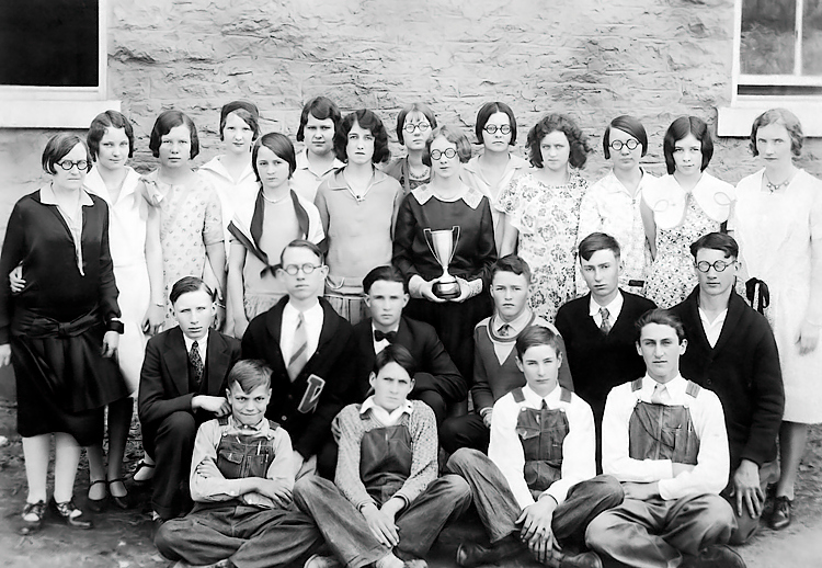 """1929 - This photo of mom and dad was made sometime in the spring of 1929 when dad was a senior at Williamsburg High School and mom was a sophomore.   Mom is holding the trophy for first place for a scholastic competition.  Dad is kneeling in the second row wearing his letter sweater.  The accompanying information says: """"In 1929 our High School Scholarship team of 22 members, pictured above, sponsored by Miss Mary McLindon (far left) and Mrs. Helen Sutherland (far right) won top honors in the Emporia District and State Class C contests and first place in the English contest over schools of all classes in the State (Kansas).  It was a tremendous victory.""""  Mom was listed as Elma Mae Staten and dad was listed as Maurice (Buster) Grigsby!  The guy had a bunch of aliases -- Jim, James, Maurice, Buster, Bud, Grig, etc."""