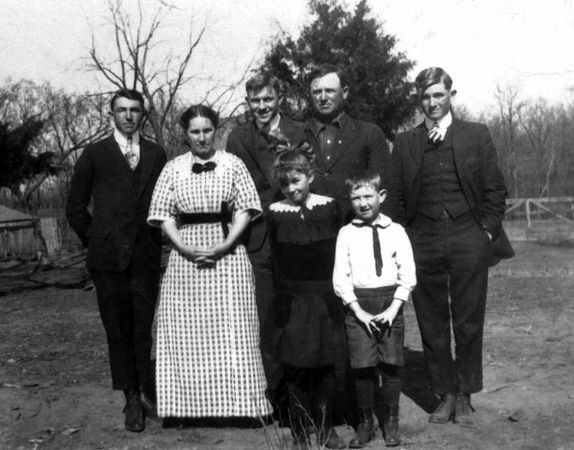"1916  - W. R. Grigsby Famly:  Lynnette Herring and our father both had copies of this photo which was taken on the same day as the other four photographs of this event.  Dad listed the people on the back of the photograph from left to right as: Charles, Lida Graves Grigsby, Theodore, Hildreth Grigsby Root, William R., James M. (our father) and Walter D.  You can see the ""Grigsby ears"" in this image!  This photo of our father reminds Bill of a later TGOD photo (#85) of Murry because of the way they hold their hands and their facial appearances including squinting their eyes.   Bill thinks, in retrospect, that grandmother Lida Grigsby saw her own baby, James M., in Murry and she saw mainly Elma Mae, our mother, in Bill.  Murry and grandmother Lida Grigsby would develop a warm friendship in Denver, but Bill never remembers having warm vibes from Lida."