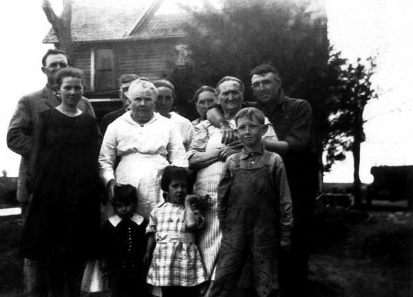 "1920 - Grigsby, Graves, Spring in Williamsburg:  Left to Right -- William Redman, Hildreth, George Selden Graves, Eva Hester Graves, Thelma Graves Herring, Lida Alma Graves Grigsby, Margaret Ellen Wilson Grigsby Spring and Charles Grigsby.  The children in front -- Leonard Herring, Lynette Herring and Dad (James Maurice ""Bud"" Grigsby) at about ten years old.  Lynnett Herring Fleming told Bill that when grandfather George Graves died in 1925 William Redman and her father, Frank (Dad called him ""old man Herring""), had a falling out over who should inherit what material goods.  Anyway, Leonard got kicked in the head by a horse and died and William Redman wouldn't let Lida Alma attend the funeral.  So in 1933 when William Redman died, ""old man Herring"" wouldn't let Thelma attend his funeral.  So the sisters, Lida Alma and Thelma, didn't talk from the time Leonard died until they had a Kansas reunion in 1941 when Lida Alma visited from Denver."