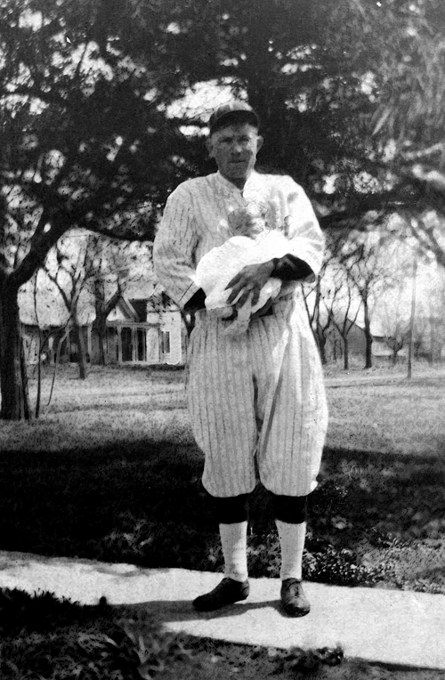 "1921 April - Photo of ""Lefty"" provided by Donald Grigsby, Theodore's Son.  In this shot Uncle Theodore is holding his second son, Max Delos Grigsby, who was born March 25, 1921, around Williamsburg, Kansas.  Dad used to tell us that Theodore could have been a big league player but wouldn't leave home.  He may be wearing the Williamsburg town team uniform?  Dad said he was called Lefty, played first base and was an excellent hitter.  Max died July 13, 1922 and Donald Lee Grigsby was born on August 22, 1922.  Theodore and Josie had another Son, Leslie Theodore, born on April 15, 1919 who died on February 13, 1920.  Bill thinks both little boys may be buried in the Mount Hope Cemetery near Williamsburg on the plot with their grandparents, William Redman and Lida Alma Grigsby."