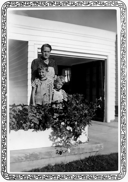 "1941 summer - This snapshot of grandmother Lida Grigsby with the two of us in front of 2566 South Washington Street was made later in the summer or fall of 1941.  We moved from 1276 South Pennsylvania sometime in early 1941 to 2566 South Washington because Bill had started first grade at McKinley School in the fall of 1940 and got a report card there for the first semester but he finished first grade at Rosedale and has a report card issued from Rosedale for the second semester in 1941.  Grandmother Grigsby lived with us at 1276 South Pennsylvania before we moved to 2566 South Washington.  Mother was working so grandmother Grigsby was our ""nanny.""  The grass looks mature and the flower box certainly wasn''t present in the earliest photograph.  Bill was 7 years old October 1941 and Murry had his 4th birthday in April, 1941.  Grandmother Grigsby had to have been a saint to put up with us.  She moved out when Bill started Junior High School in the fall of 1946."