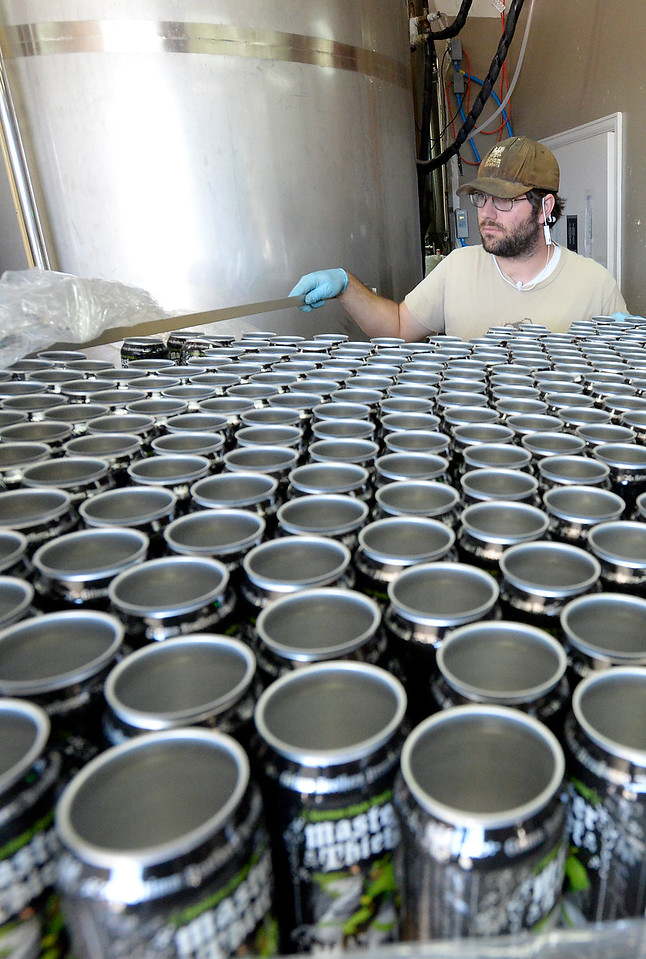 Michael Becker, head brewer for Grimm Borthers Brewhouse, moves empty cans into place while canning beer Monday, Oct. 10, 2016, at the brewery in east Loveland. Grimm Brothers won a gold medal for its Little Red Cap at the 2016 Great American Beer Festival in Denver on Saturday. This is the fourth major medal for Little Red Cap, coming in the German-style Altbier category.  (Photo by Jenny Sparks/Loveland Reporter-Herald)