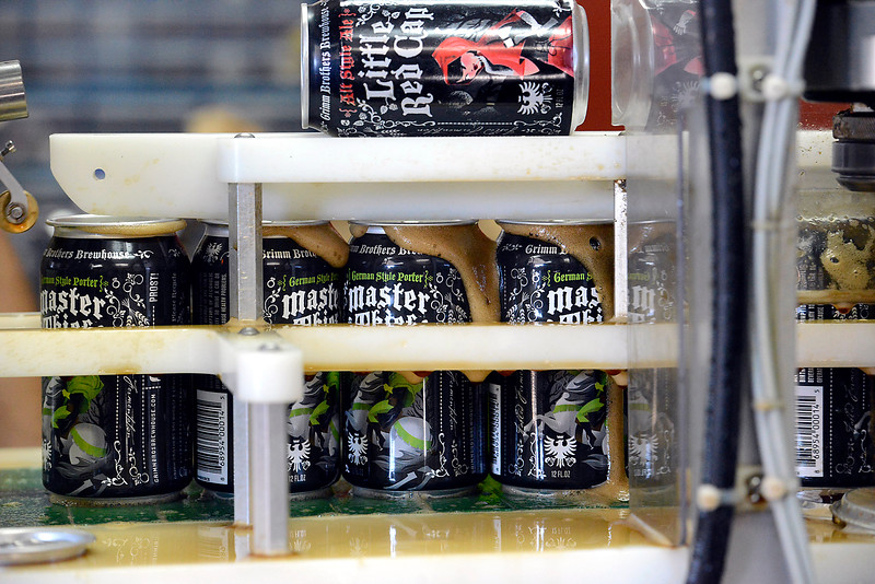 Foam overflows out of the cans as the lids are attached to the Grimm Borthers Brewhouse Master Theif German style porter beer during the canning process Monday, Oct. 10, 2016, at the brewery in east Loveland. Grimm Brothers won a gold medal for its Little Red Cap at the 2016 Great American Beer Festival in Denver on Saturday. This is the fourth major medal for Little Red Cap, coming in the German-style Altbier category.  (Photo by Jenny Sparks/Loveland Reporter-Herald)