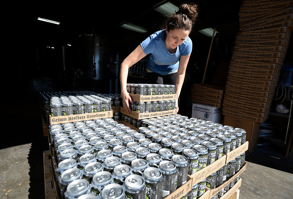 . Laura Pilato, brewing baroness for Grimm Borthers Brewhouse, stacks cases of their Master Thief German style porter beer on a palet while canning Monday, Oct. 10, 2016, at the brewery in east Loveland. Grimm Brothers won a gold medal for its Little Red Cap at the 2016 Great American Beer Festival in Denver on Saturday. This is the fourth major medal for Little Red Cap, coming in the German-style Altbier category.  (Photo by Jenny Sparks/Loveland Reporter-Herald)