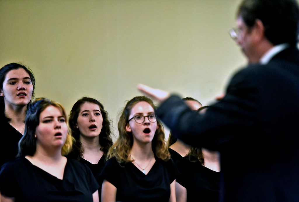 . GD Music Director Tim Savoy directs members of the Groton Dunstable Chamber Choir performing at th Leominster Public Library. SUN/ David H. Brow