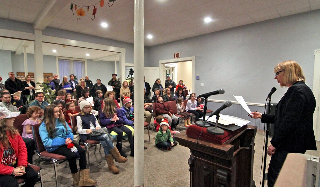 . Giving her greetings at the Groton Interfaith Council Community Tree Lighting is Council member Judy Nauman on far right. SUN/ David H. Brow
