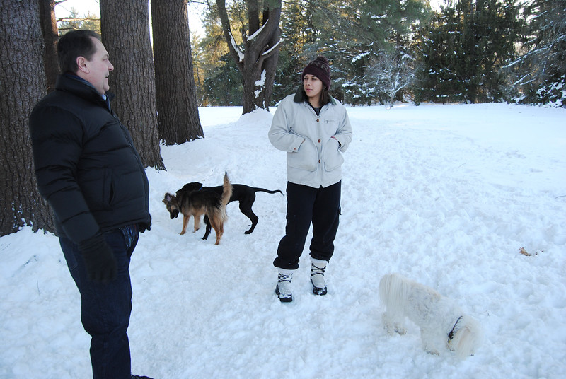 NASHOBA VALLEY VOICE/ANNE O'CONNOR<br /> Doug Eames and Kira Shaikh chat while the dogs play. Tucker, the bichon/pom mix owned by Eames plays hard even with just one hip. Dog walkers are welcome at Groton Place, the property owned and managed by the New England Forestry Foundation.