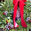 Groton Woman's Club past president Nancy Olson, peeks through a Holiday wreath, one of many to be up for sale at the Clubs 14th Annual  Holiday Greens Sale at Williams Barn in Groton. SUN/ David H. Brow