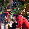 Adding to the hundreds of Holiday wreaths and other items is Pat Bennett of Groton and a member of the Groton Woman's Club, getting ready for their 14th annual Holiday Greens sale. SUN/ David H. Brow