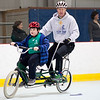 Declan Wilkins, 9, of Lowell (left) rides a tandem bicycle with iCan Shine's Kent Husa on April 20, 2016 at an Emerson Hospital camp that teaches children with special needs how to ride a bicycle. Chris Lisinski/Nashoba Valley Voice