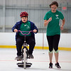 9-year-old Declan Wilkins of Lowell (left) cruises on a training bike alongside UMass Lowell senior Hailey Tompkins, who volunteered on April 20, 2016 along with 51 other members of her exercise physiology class to teach bike-riding to children with special needs. Chris Lisinski/Nashoba Valley Voice