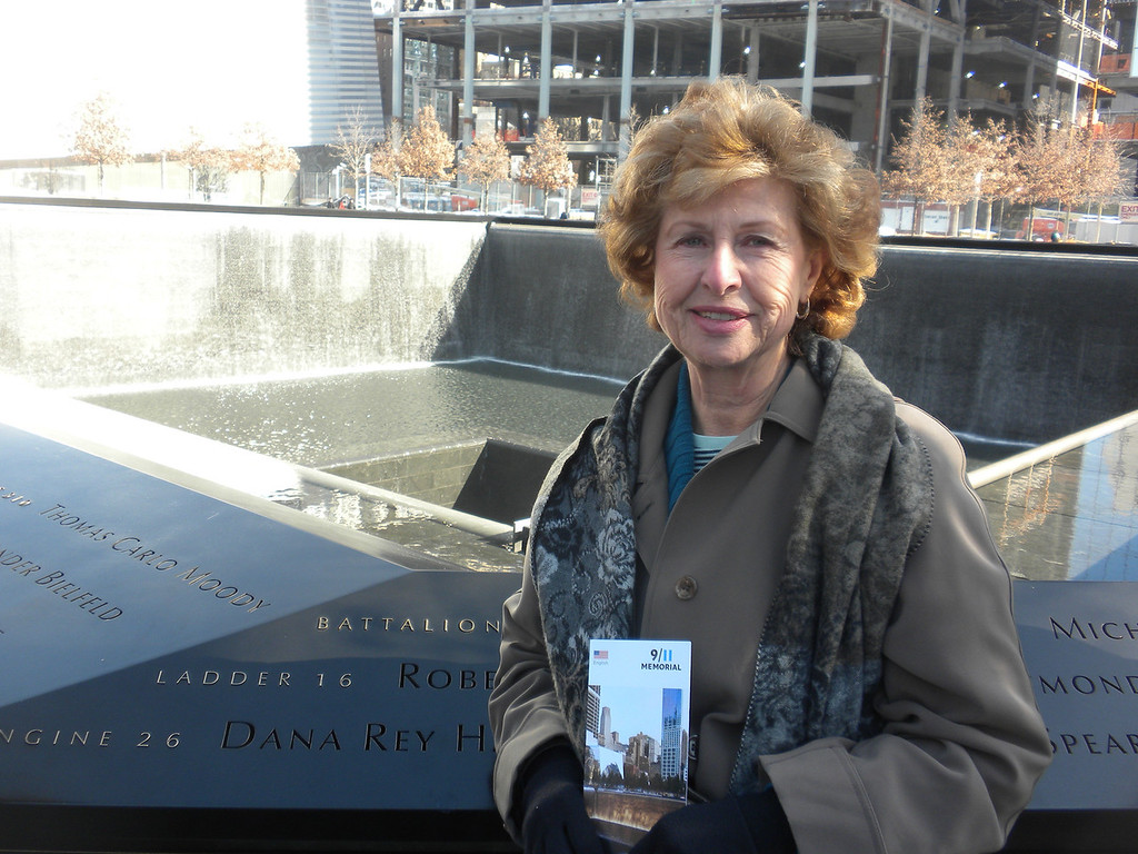 Betty standing in front of one of the two fountains at the 911 Memorial. The two Fountain represent the two Towers of the World Trade Center. The water symbolizes the people's cries which never will stop and as the water falls down inside the ground that symbolizes the emptiness left by those who died. The Fountains are also reflecting pools symbolizing peoples remembrances. The many tree planted in the adjacent courtyards are symbols of new life!