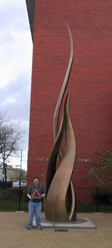 """Fire at the site of the origin of the Great Chicago Fire of 1871 [4/25/2004] <p> Chuck Carroll and Fire at the """"Pillar of Fire"""" sculpture."""