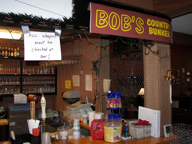 """""""All weapons must be checked at bar!"""" sign over bar"""
