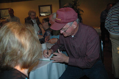 "Billy Ashabraner signs a copy of his book ""insights Into Racing""."