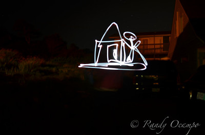 I took this picture while giving a family member, Alyssa Latham, a lesson in light painting photography.  Alyssa is drawing the outline of a house and stick figure in the air with an led light.