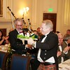 Burns Night: Sir Jeremy Bell playing bagpipes and Ken Smith with can of haggis in Dining Room